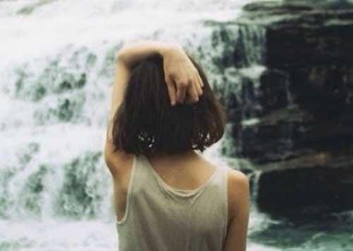 女性の後ろ姿と滝