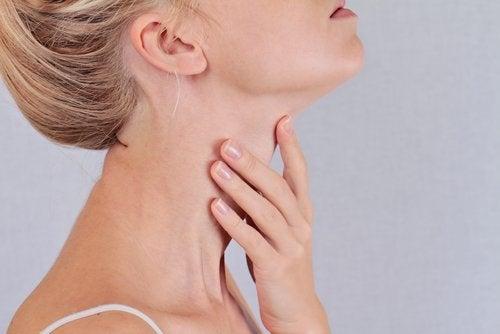 喉を押さえる女性