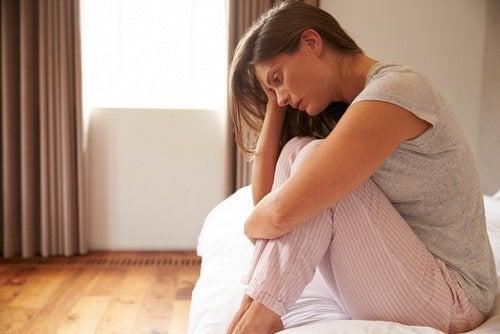 ベッドに座って憂鬱そうな女性