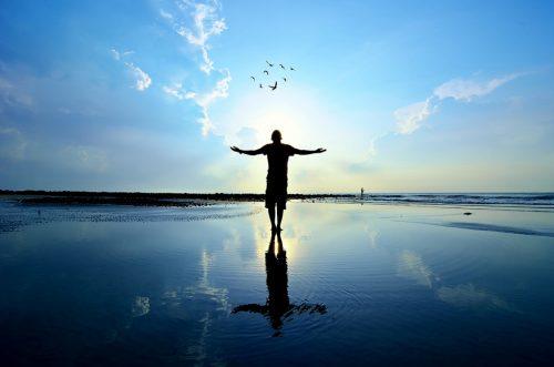 大きな空に向かって手をひろげる人