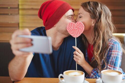 ハートのぺろぺろキャンディーを口にあてキスするカップル