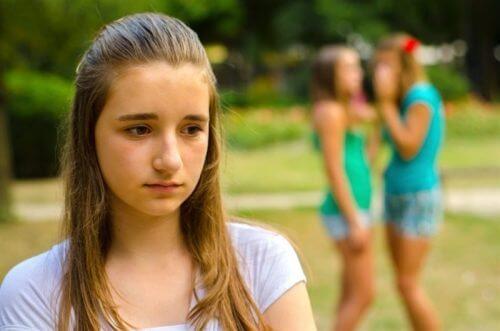 悲し気な女の子 後ろのほうで他の子が悪口を言っている