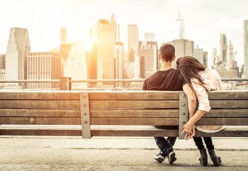 ベンチに座り街を眺めるカップルの後ろ姿