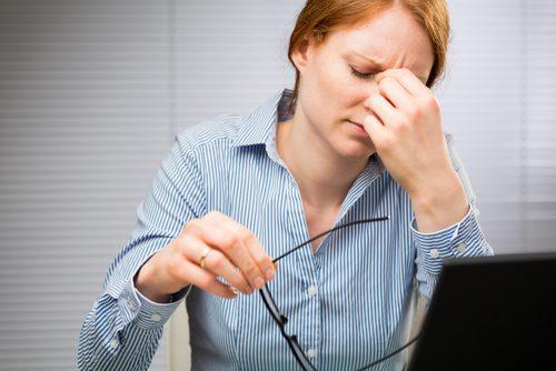 パソコンの前で眼鏡をはずし目に手をやる女性