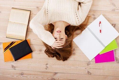 ノートや本に囲まれ、ストレスを感じる女性