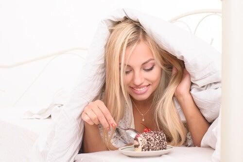 ふとんをかぶってケーキを食べる人