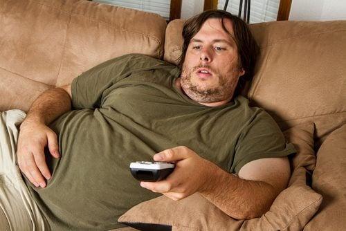 ソファーでリモコン操作する肥満の人