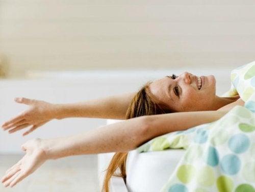 ベッドの上で笑顔でのびをする女性