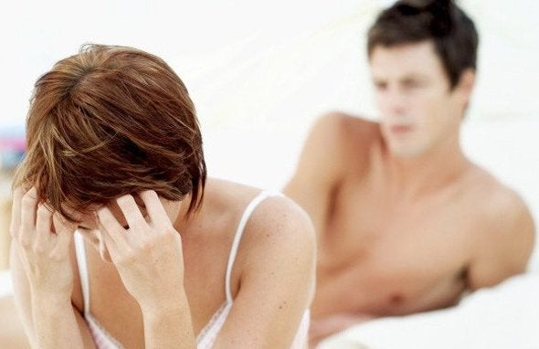 ベッドで頭を抱えてうつむく女性と背後に男性