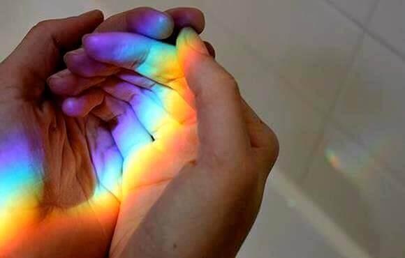 手のひらに虹が反射している