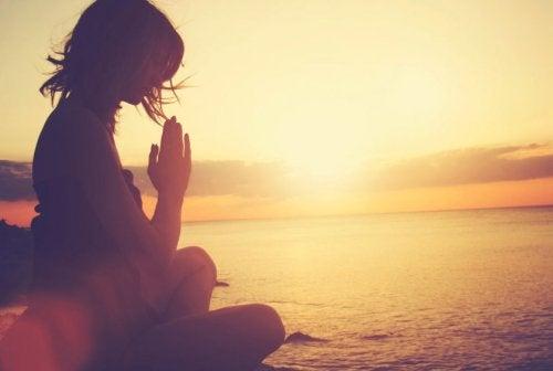 夕日の沈む海辺で瞑想する