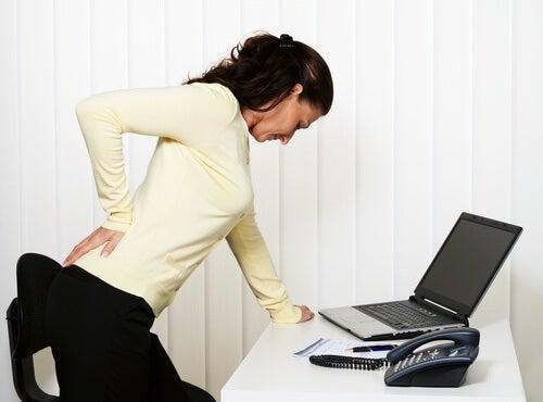 パソコンの前で腰痛に耐える女性