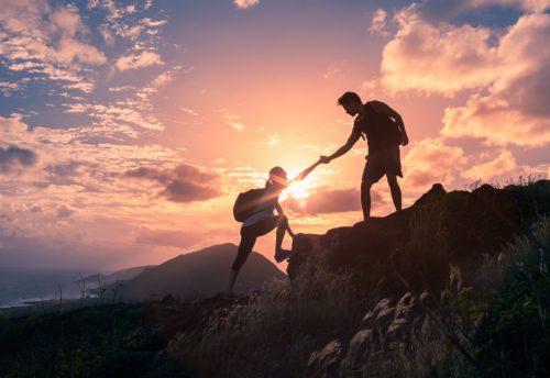 夕日を背景に山登りする人たち