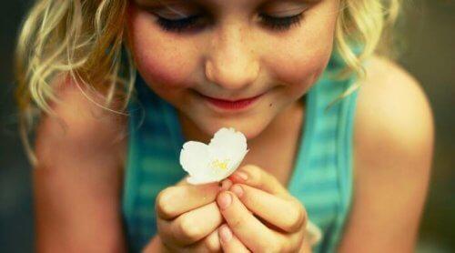 花を一輪持っている金髪の女の子