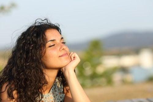 目をつぶり屋外でリラックスする女性