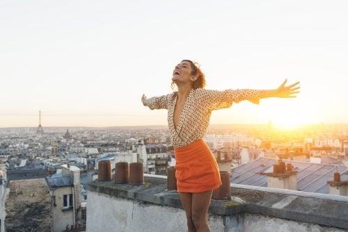 屋上で空に向かって両腕をひろげる女性