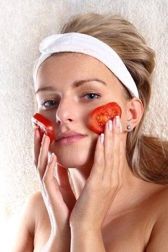 トマトを顔にあてる女性