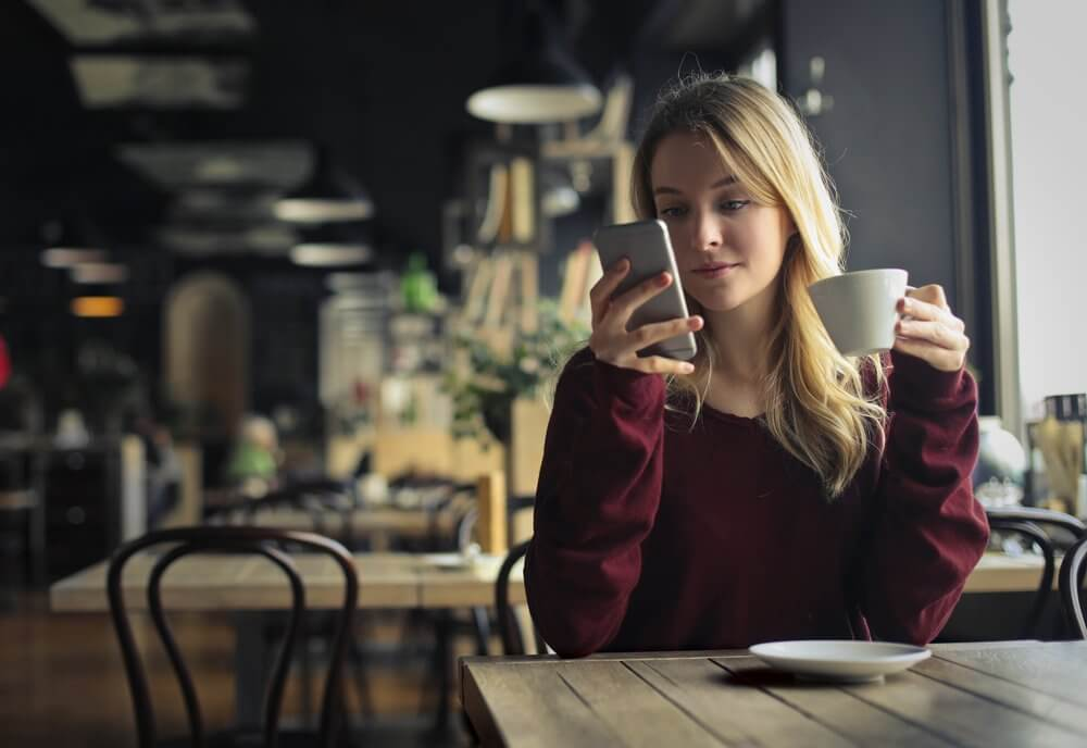 カフェで携帯を見る女性