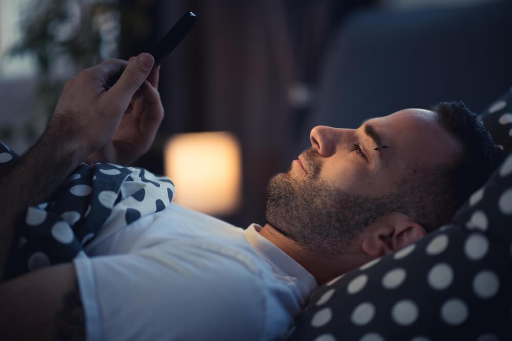 ベッドで携帯を眺める男性
