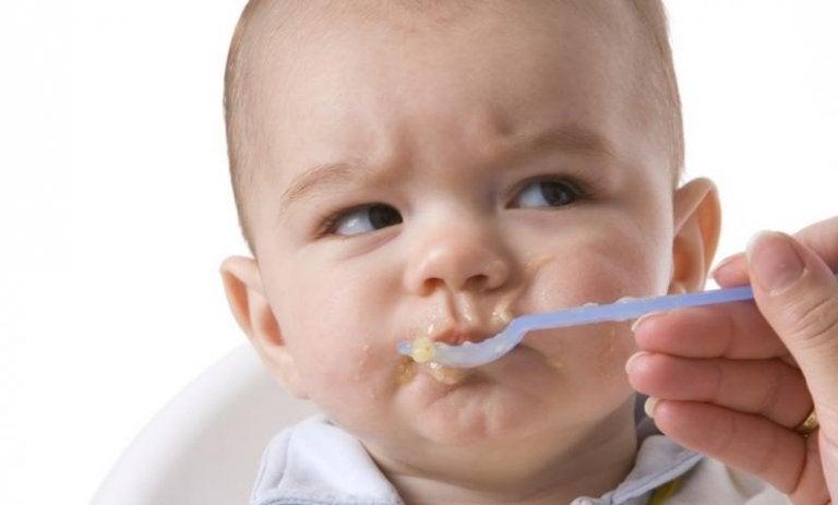 離乳食を食べて顔をしかめる赤ちゃん