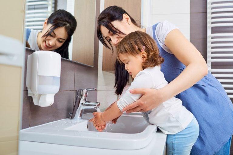 母親と手を洗う幼児