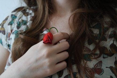 赤い花を胸にあてた女性