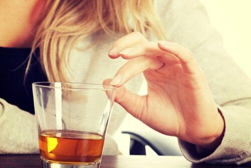 お酒のグラスを触る手