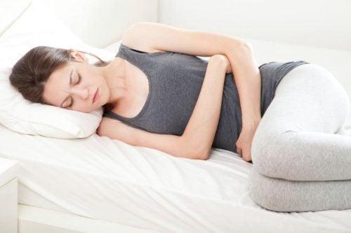 ベッドでお腹を抑える女性