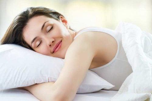枕を抱いてほほ笑み眠る女性