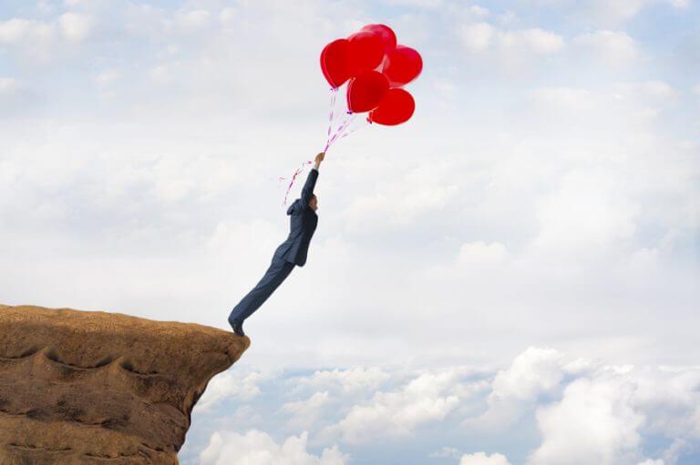 風船にぶら下がって崖から飛ぼうとする人