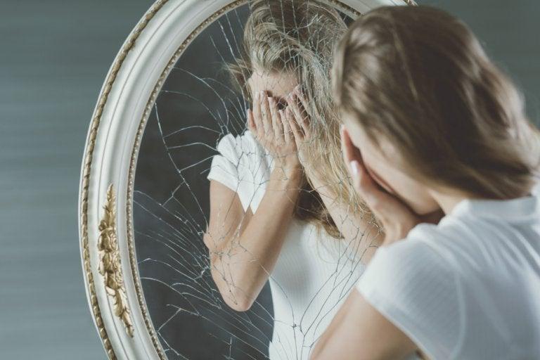 割れた鏡の前で顔を覆う女性