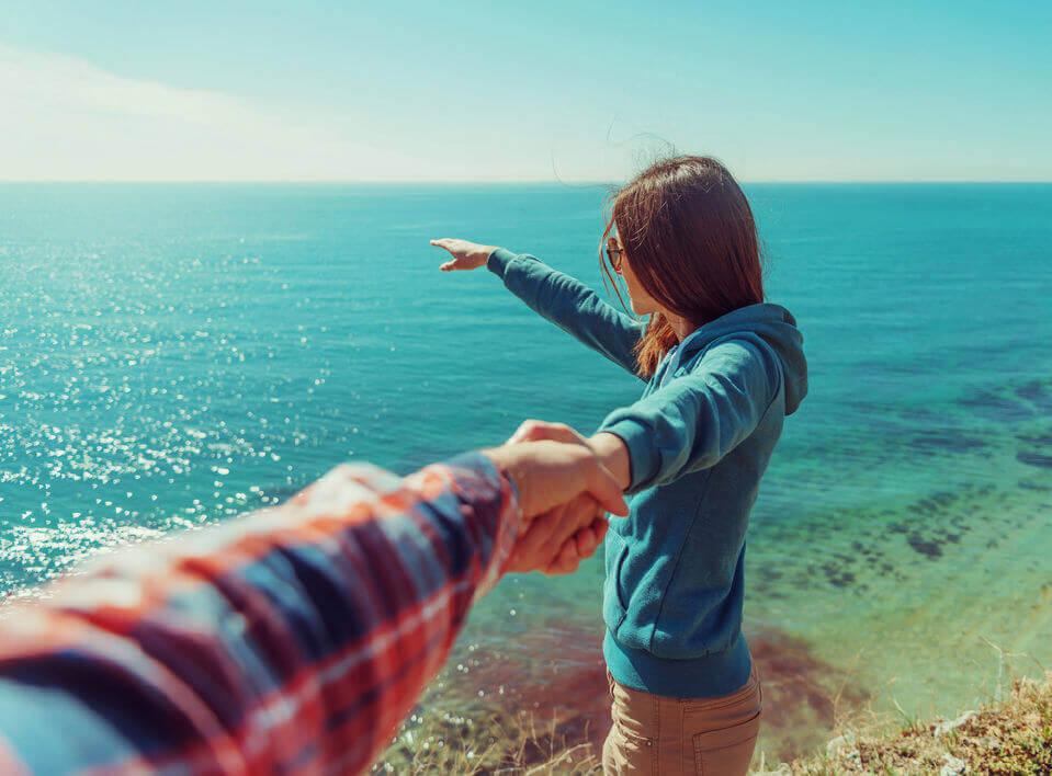 海の前で男性の手を引く女性