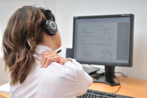 パソコンの前で肩に手をやる人