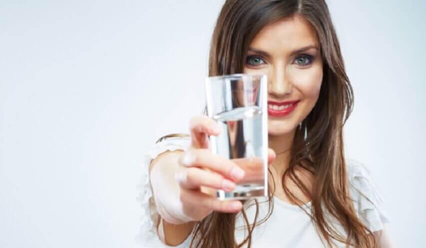 水の入ったグラスを持つ女性