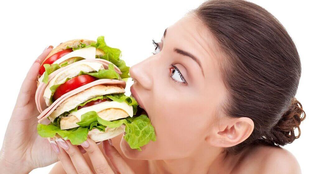 大きなサンドイッチを食べる女性