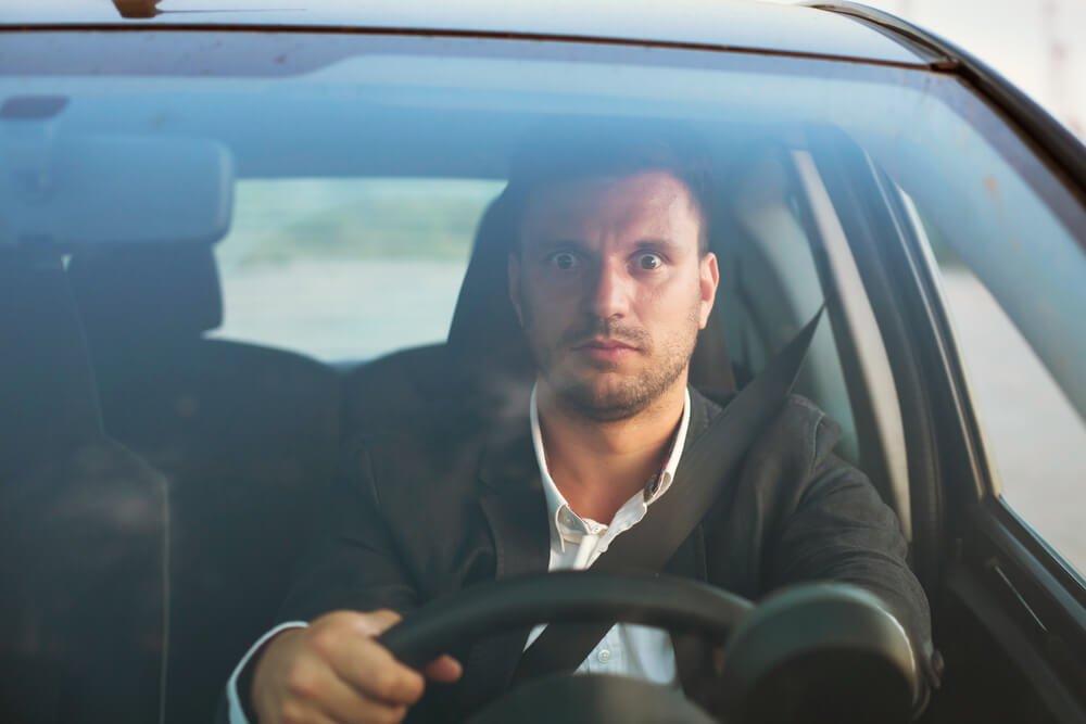目を見開いて運転する男性
