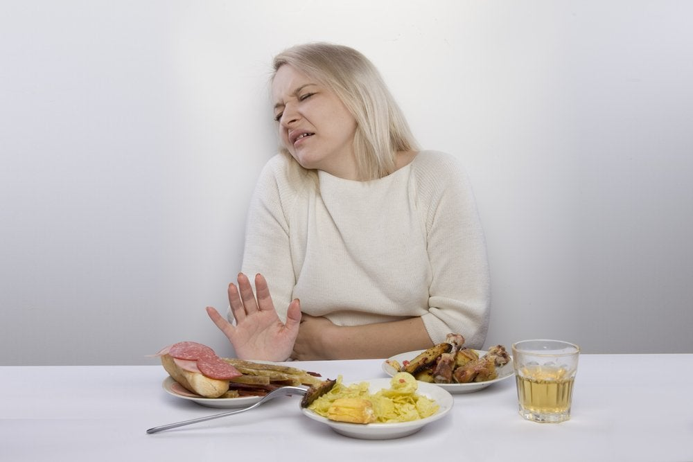 重い食事を前に顔をしかめる女性