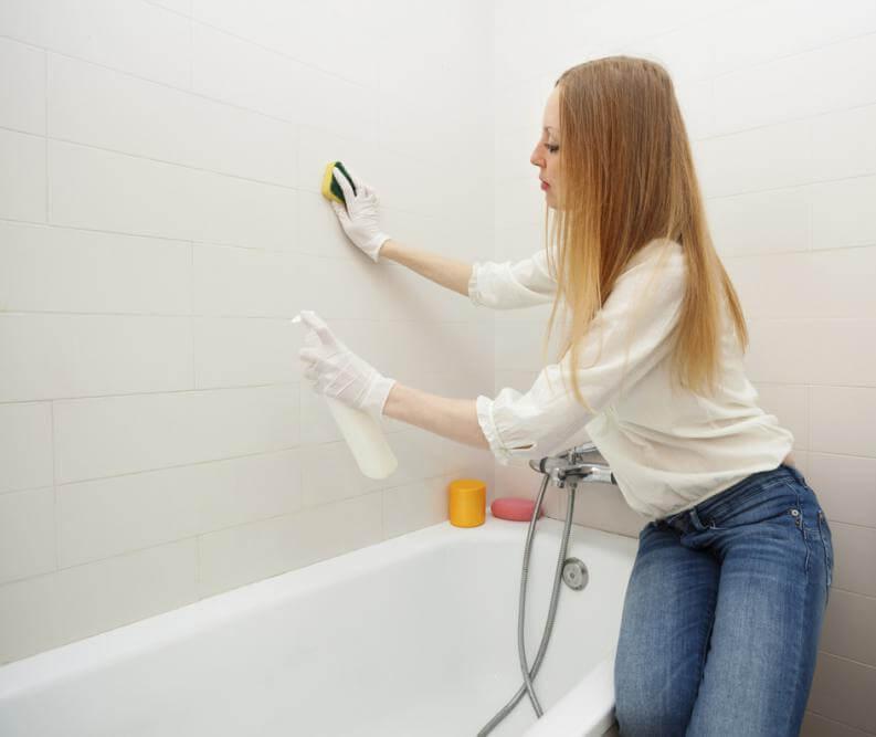 浴室の壁を掃除する女性