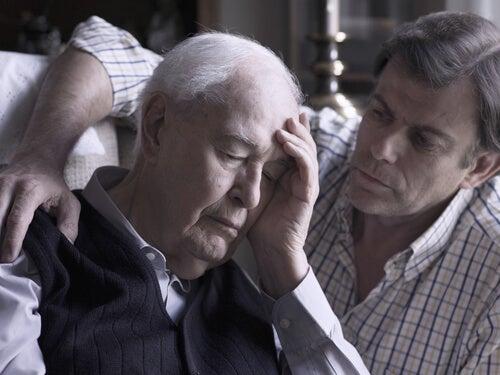 頭を抱える老人と見守る男性