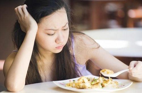 料理を前に不機嫌な女性