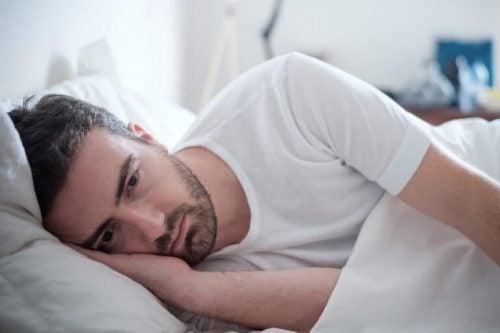 ベッドに横たわり目を開けている男性
