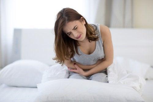 白いベッドの上で腹部の痛みに耐える女性
