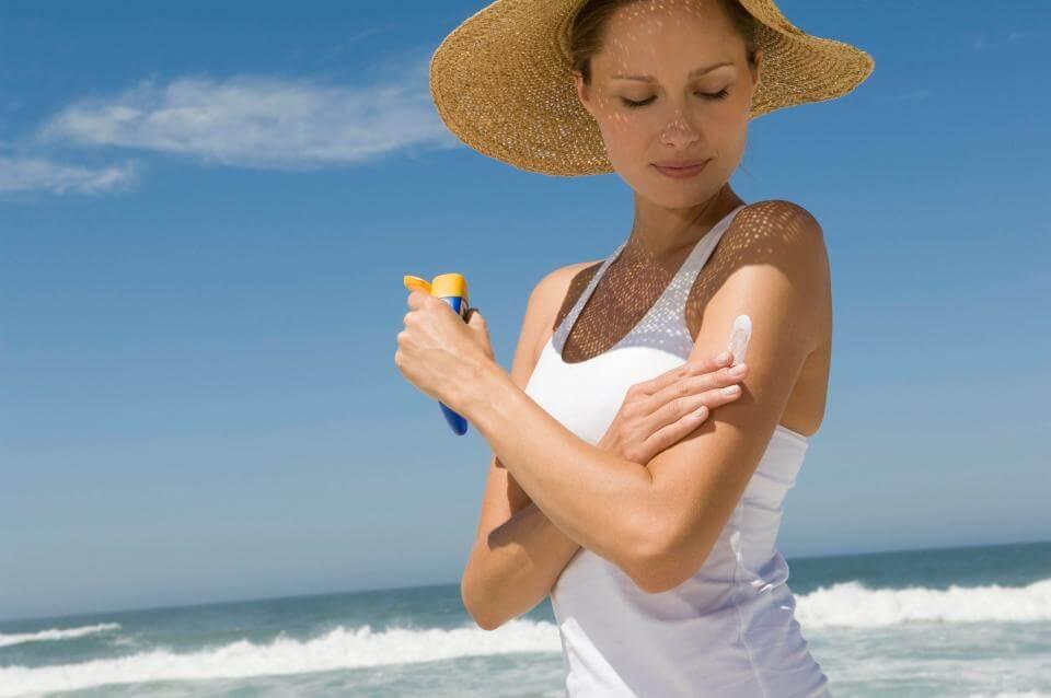 海で日焼け止め剤を塗る女性