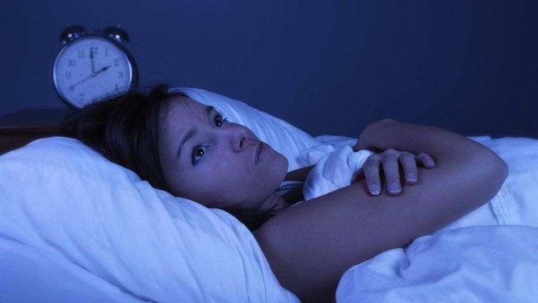 ベッドで眠れず目を開けている女性