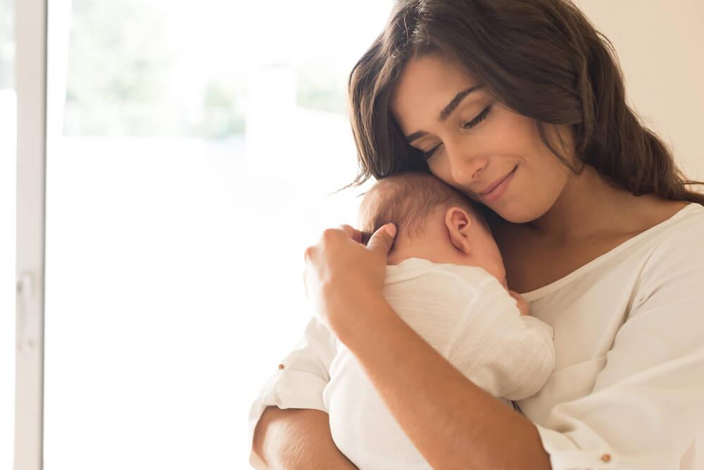 赤ちゃんを抱き目を閉じる女性