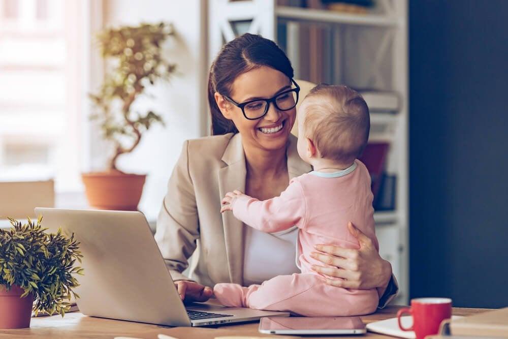 PCと赤ちゃんに向き合う女性