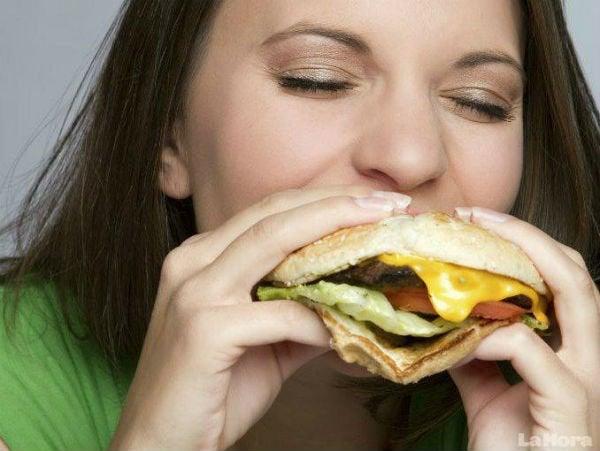ハンバーガーをほおばる女性