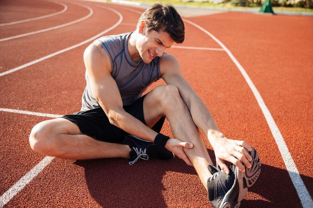 運動場でふくらはぎが痙攣している人