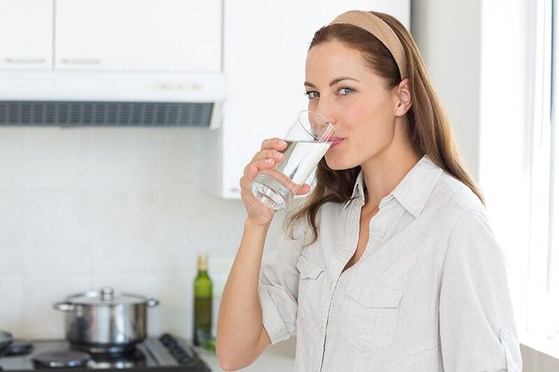 コップの水を飲む女性