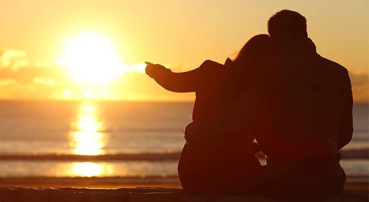 海辺で夕焼けを見るカップル